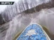俄罗斯男子在被水淹没的森林里冒险冲浪